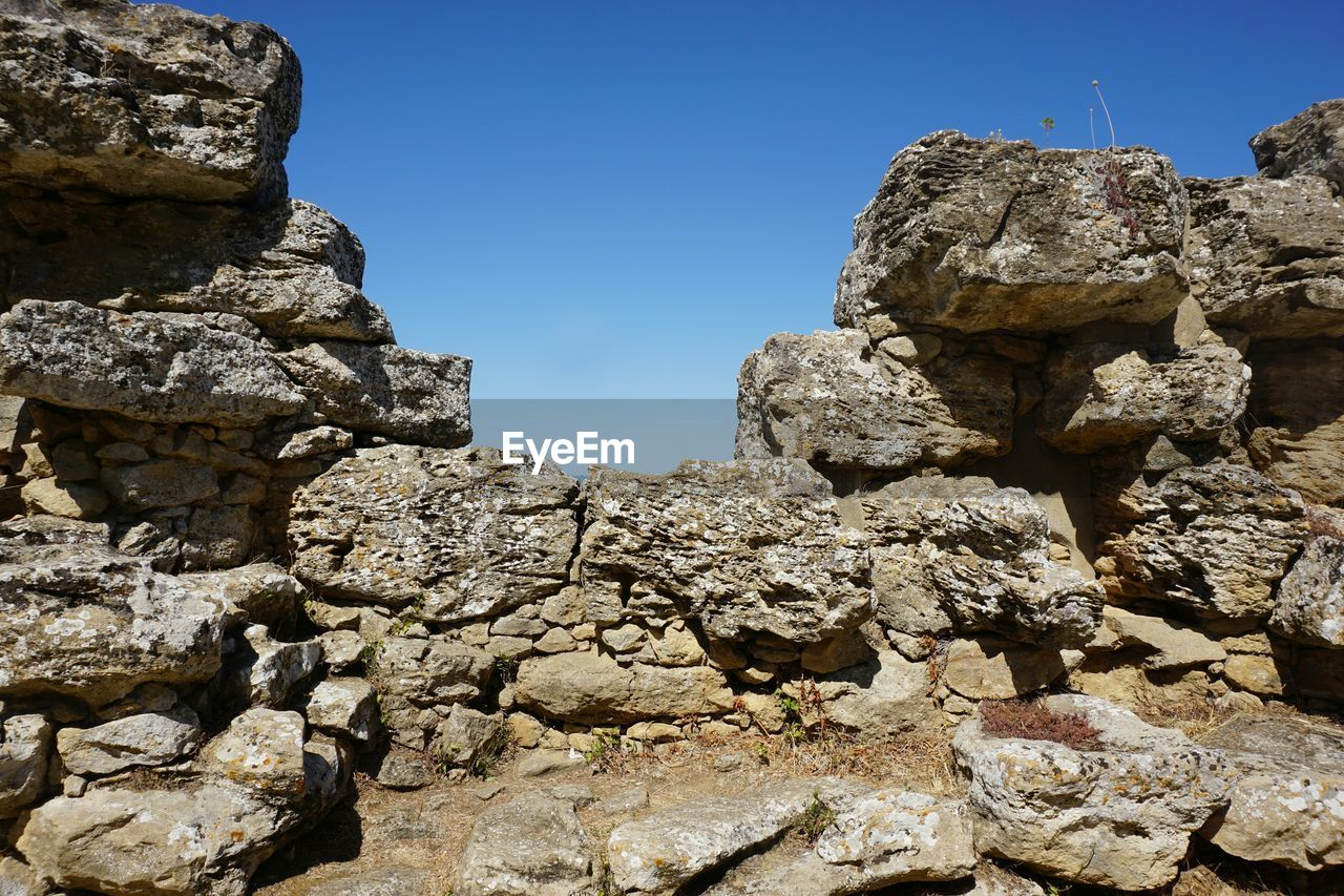 sky, rock, solid, nature, no people, clear sky, day, rock - object, low angle view, architecture, history, built structure, blue, sunlight, the past, outdoors, rock formation, ancient, stone wall, old ruin, ancient civilization