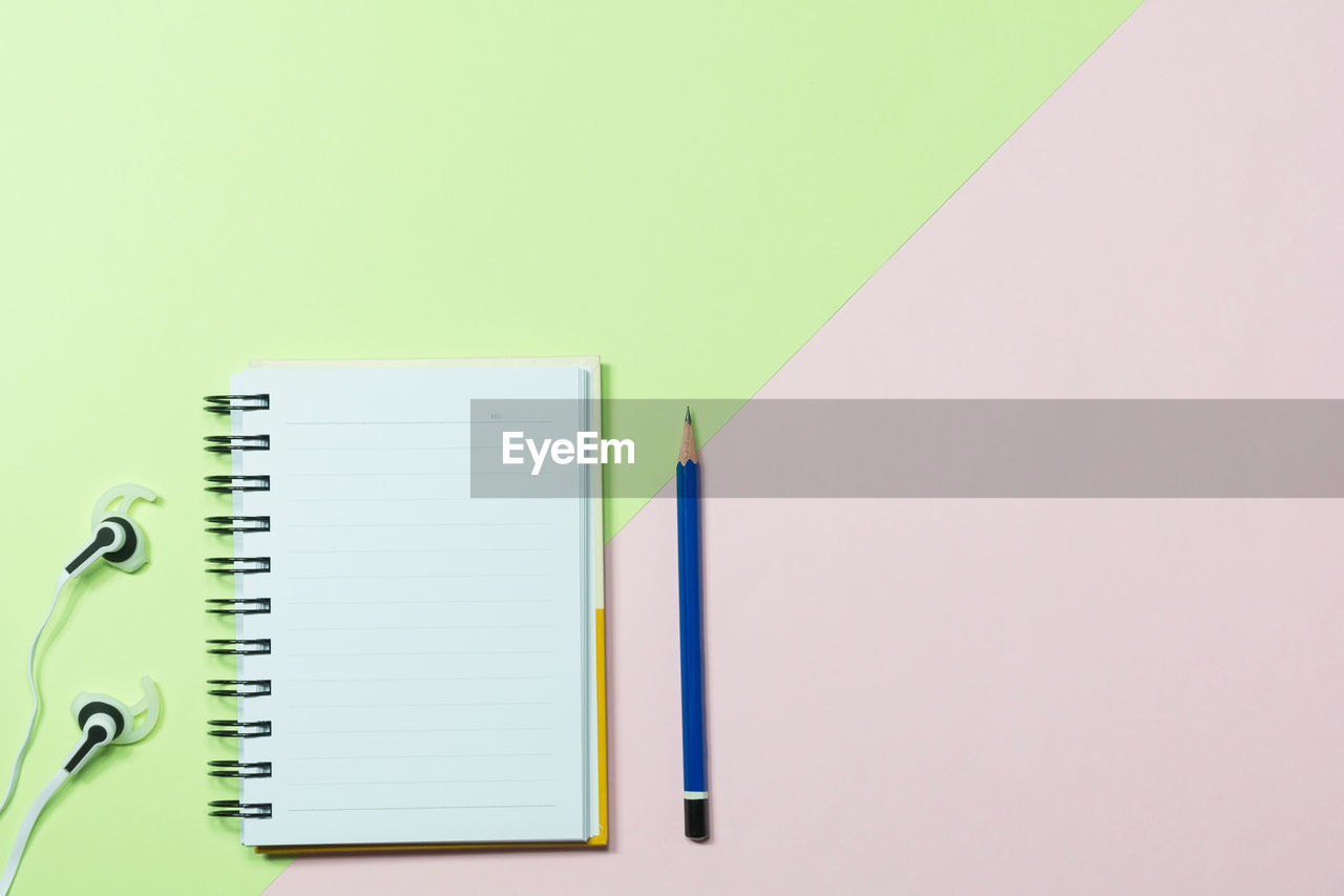 High angle view of book with pencil and headphones on colored background