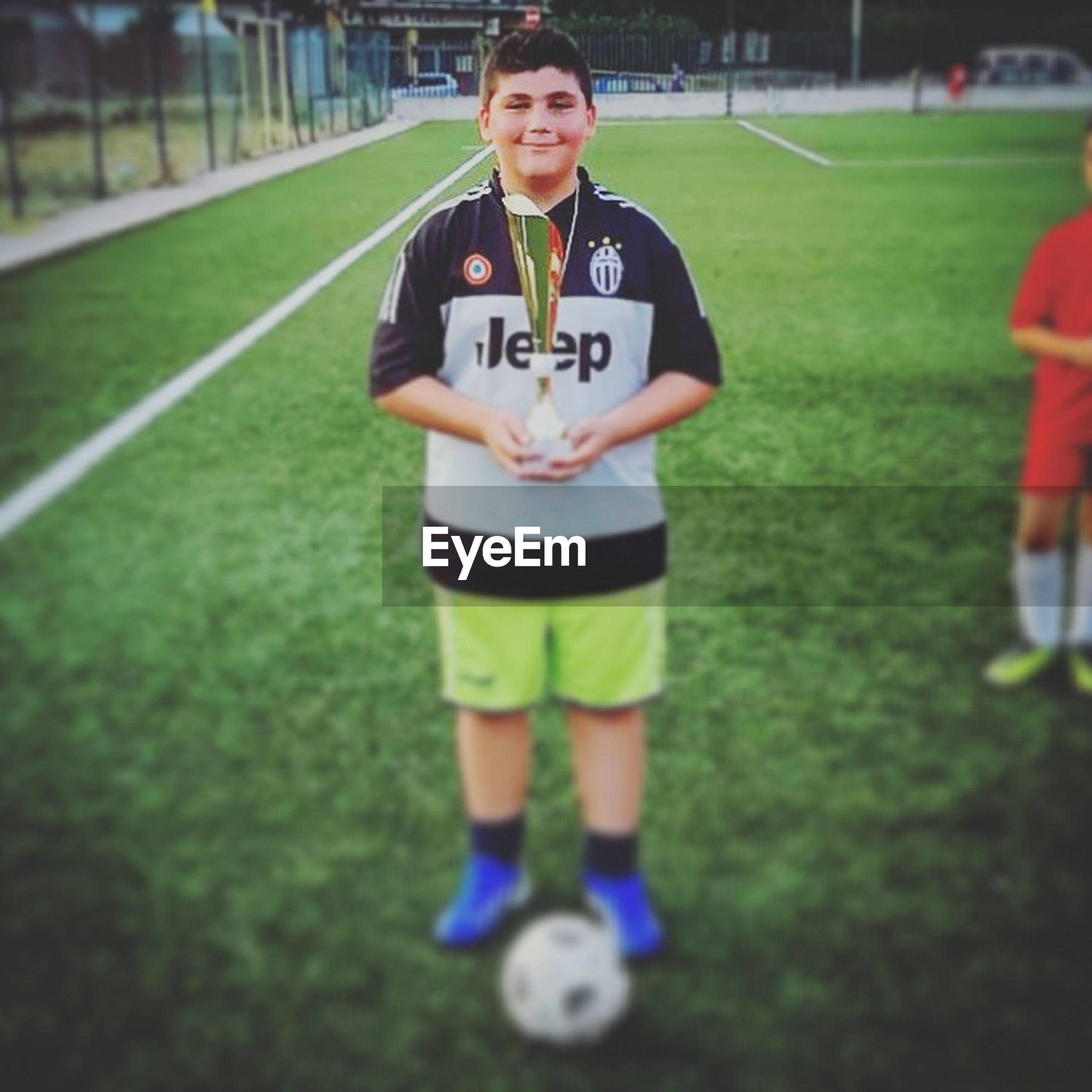 sport, number, childhood, grass, full length, sports clothing, front view, team sport, playing, competition, one person, outdoors, sports uniform, day, physical education, soccer, competitive sport, soccer field, playing field, sports team, real people, soccer uniform, people