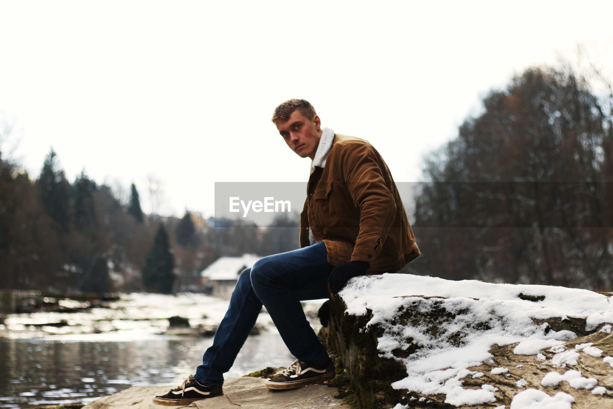 Portrait young man sitting on snow against trees