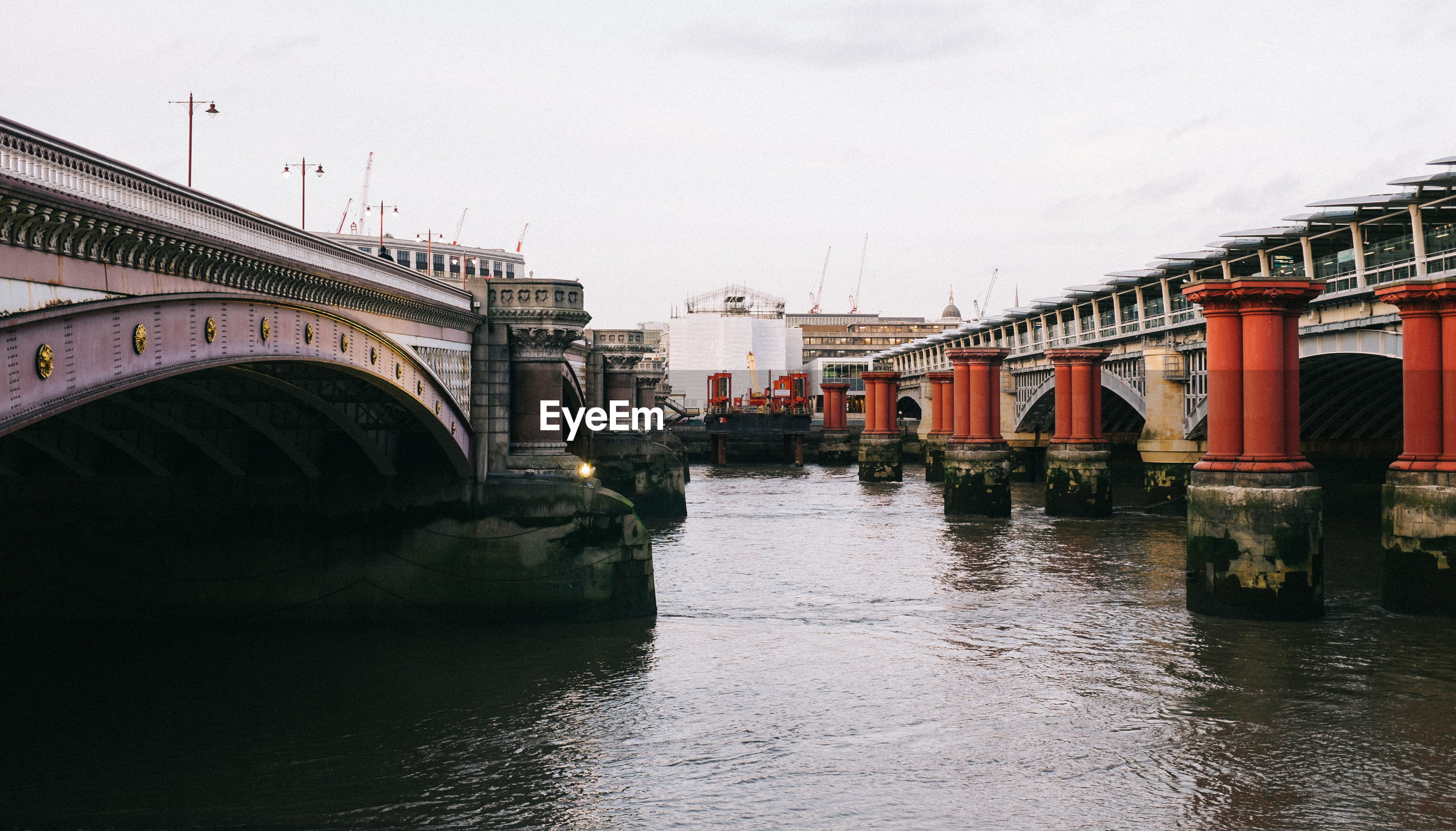 Arch bridges over river in city against sky