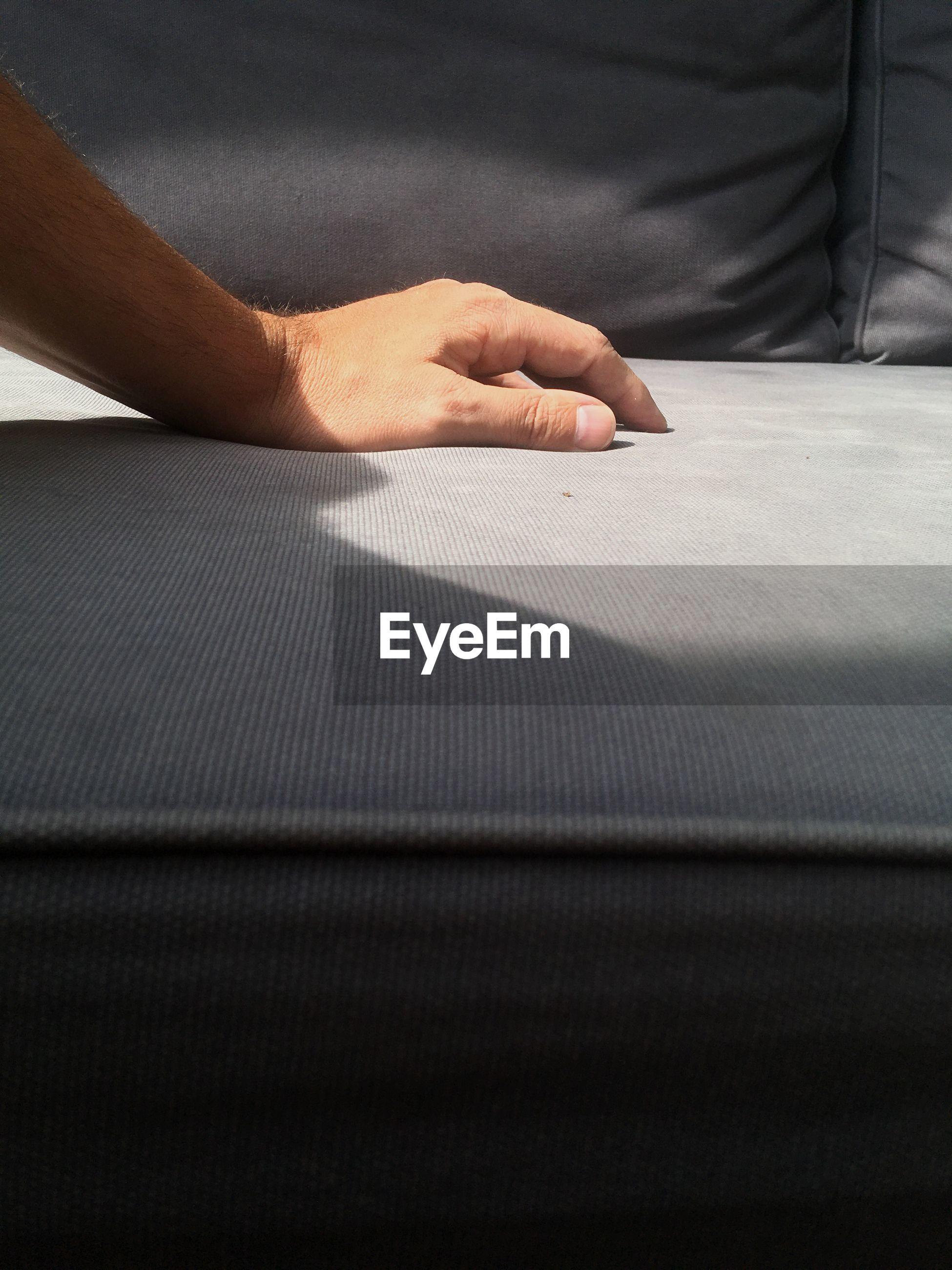 Close-up of hand on sofa