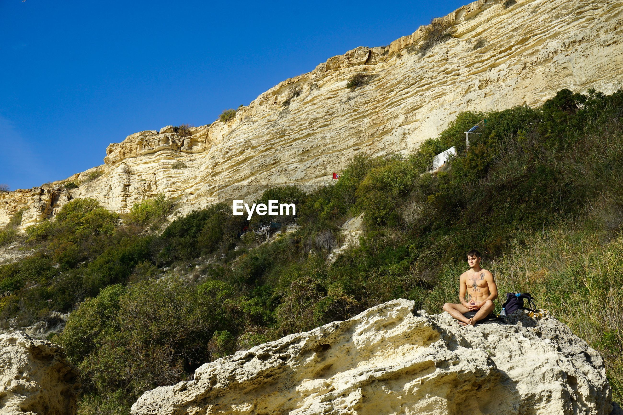 WOMAN SITTING ON ROCK BY MOUNTAIN AGAINST SKY