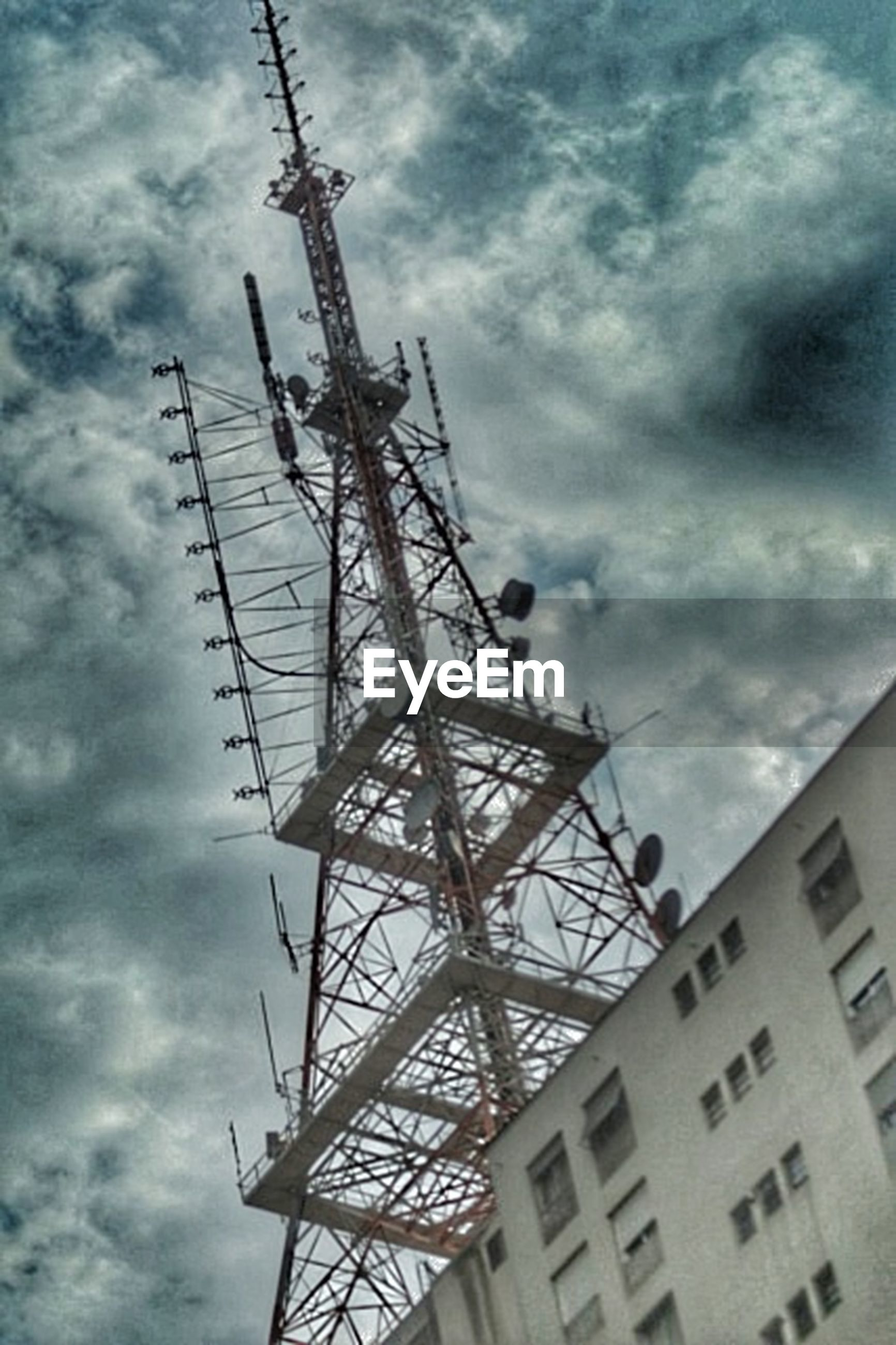 low angle view, sky, cloud - sky, built structure, cloudy, architecture, construction site, development, crane - construction machinery, cloud, fuel and power generation, electricity pylon, tall - high, metal, technology, power supply, electricity, day, construction, building exterior