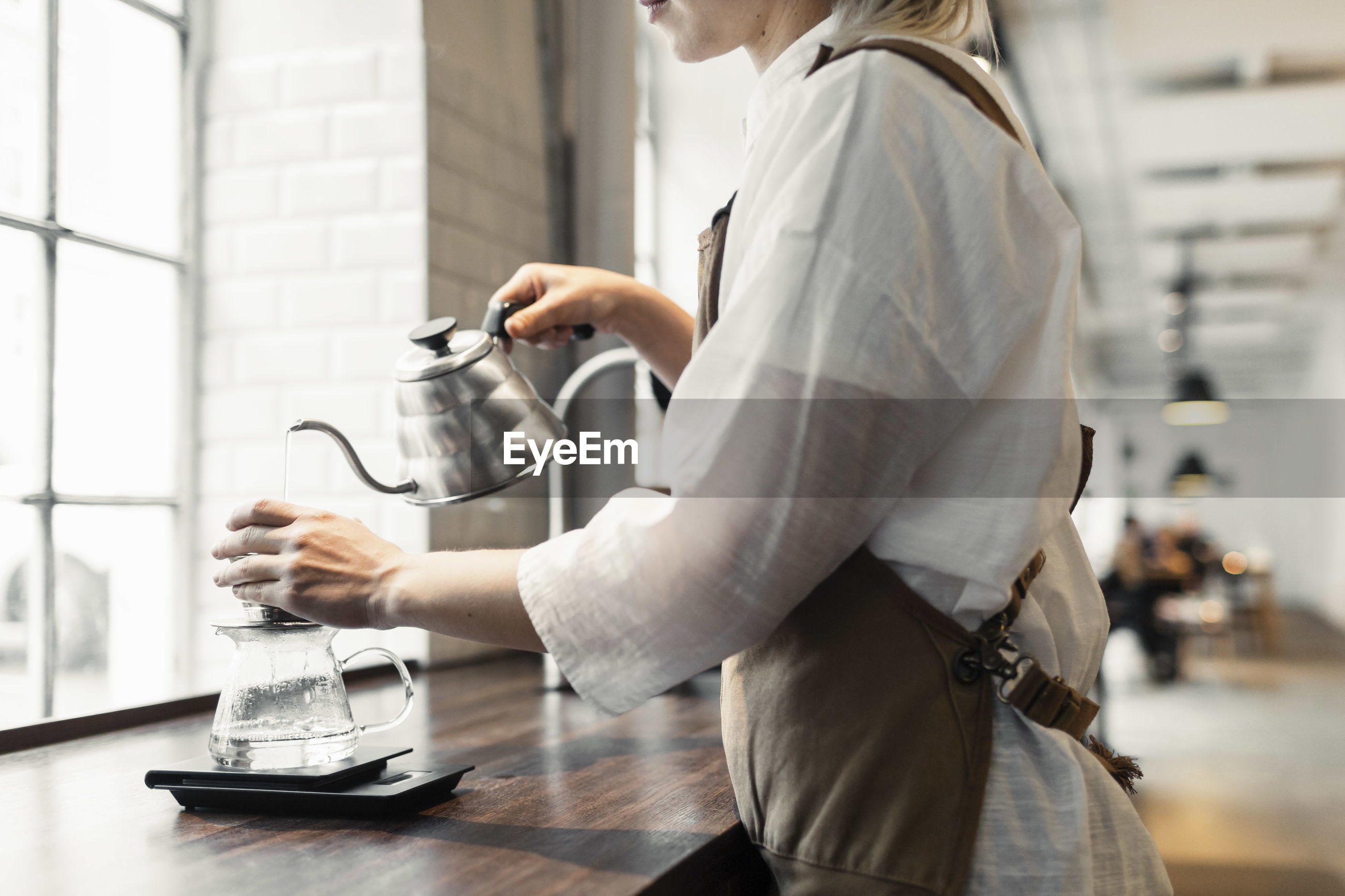SIDE VIEW OF WOMAN HOLDING COFFEE CUP IN KITCHEN