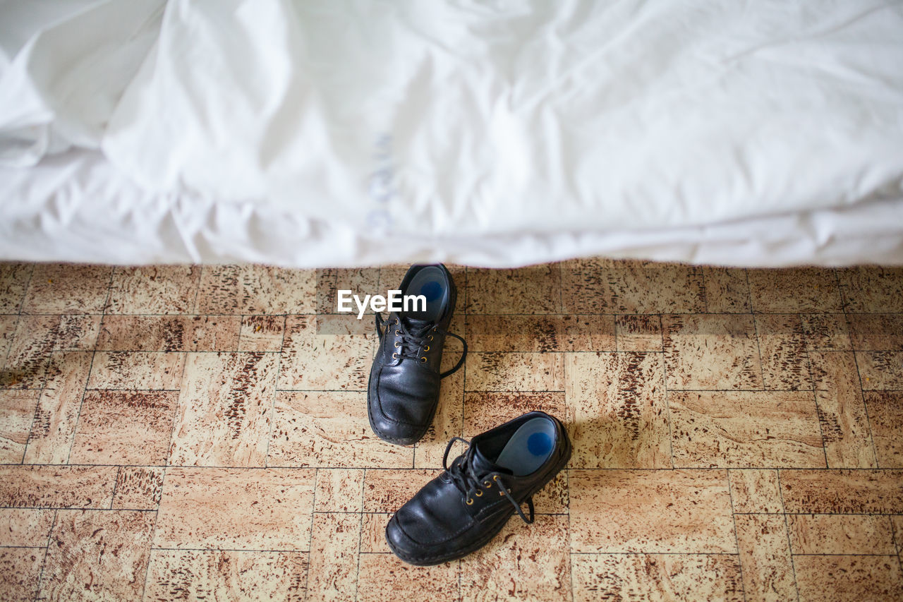 High angle view of shoes by bed on floor