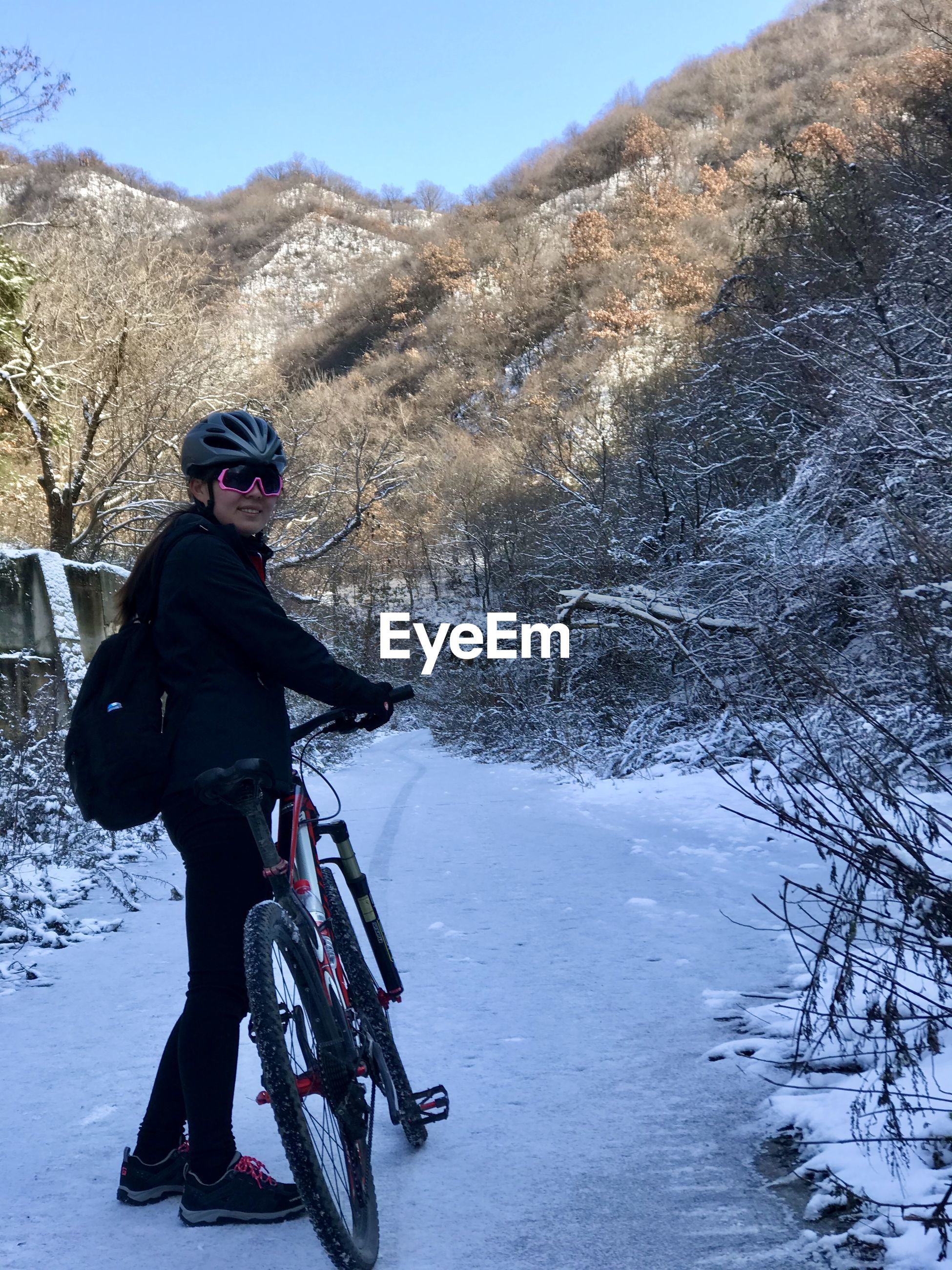 Full length of woman standing with bicycle during winter