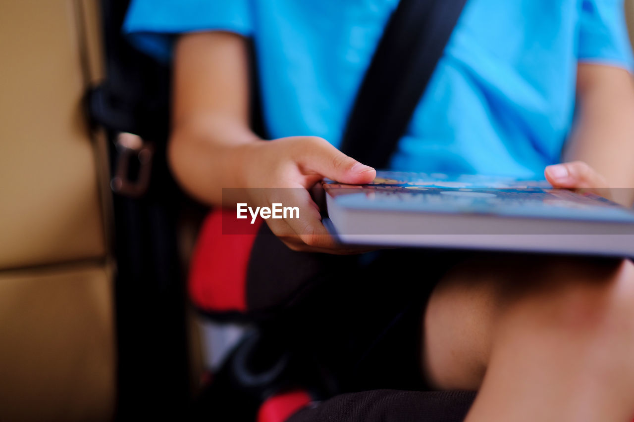 Midsection of boy holding book while sitting in car
