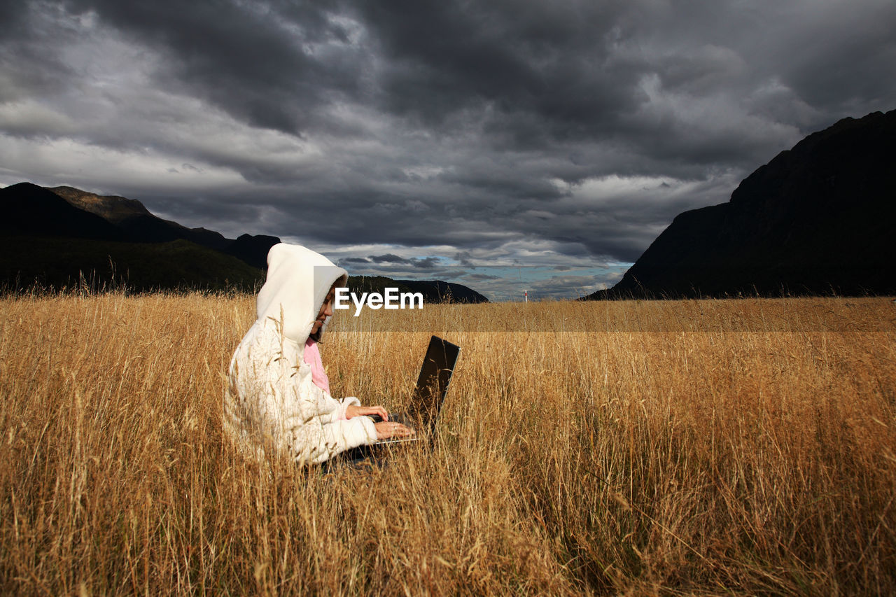 Mid Adult Woman Using Laptop While Sitting On Grassy Field Against Cloudy Sky