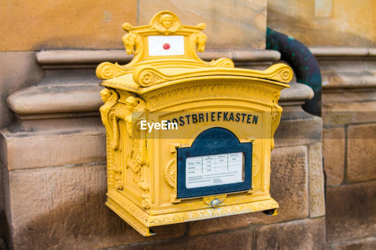 Yellow mailbox on wall