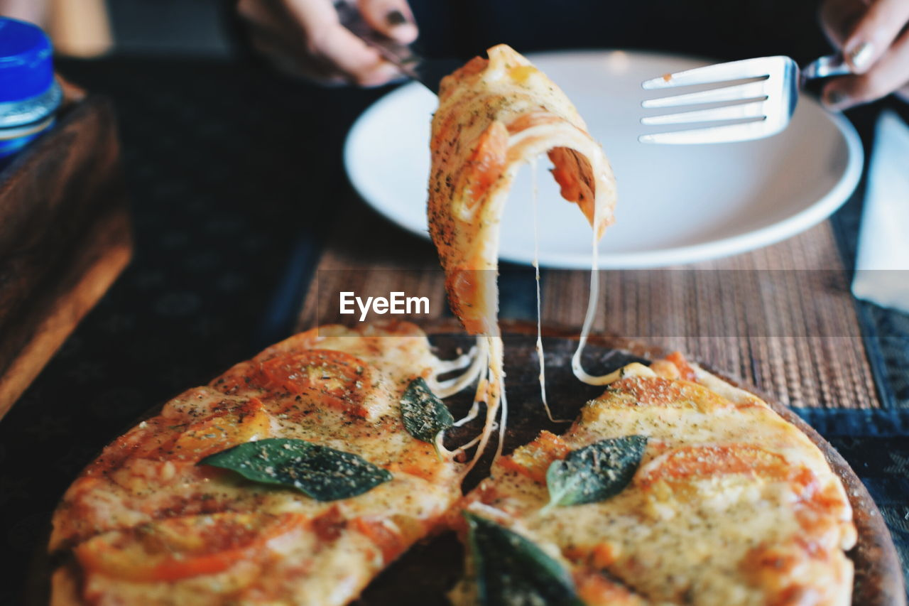Close-up of hands holding pizza with fork and knife on table