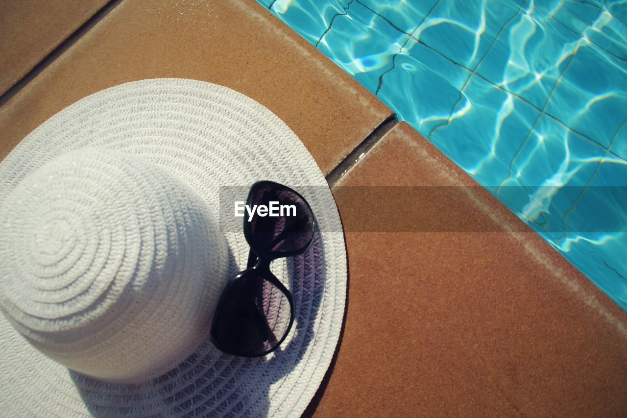 Overhead View Of Sun Hat Sunglasses On Swimming Pool