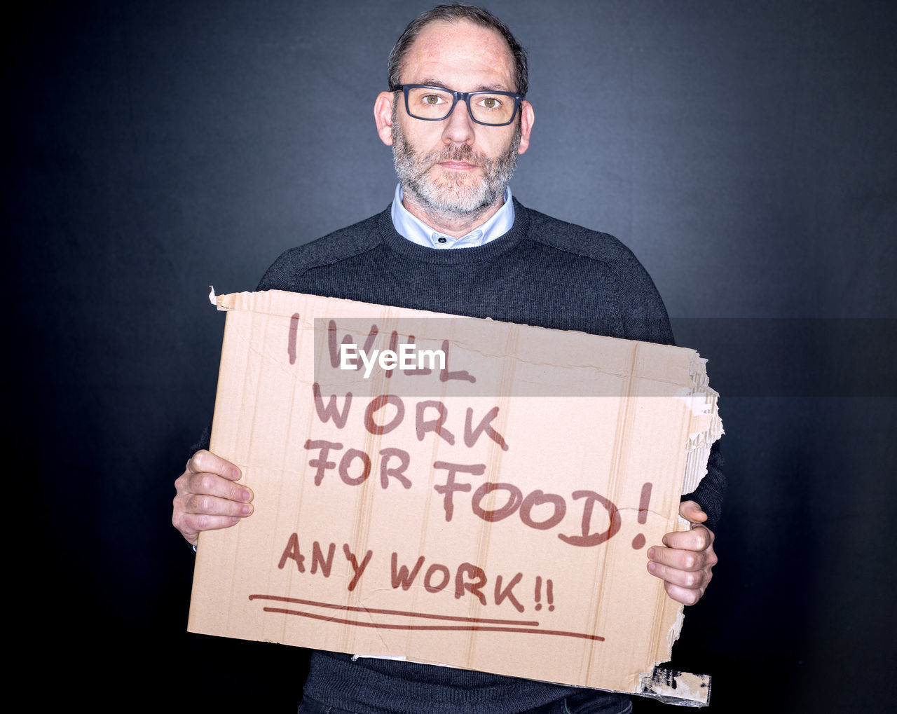 one person, communication, sign, casual clothing, front view, text, western script, beard, holding, men, indoors, sadness, males, mature adult, facial hair, eyeglasses, glasses, mature men, social issues, depression - sadness, message, black background, unemployment, economy