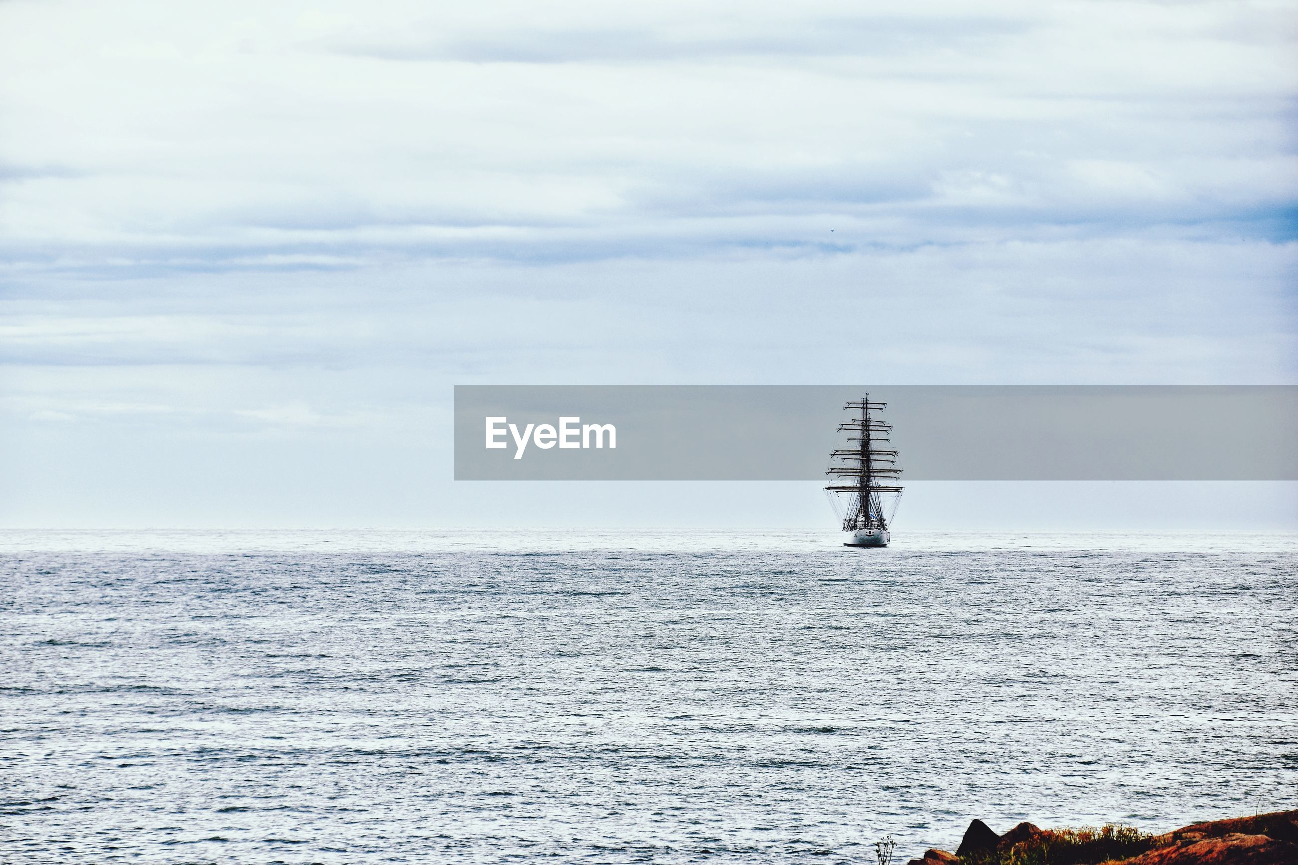 SAILBOAT ON SEA BY LIGHTHOUSE AGAINST SKY