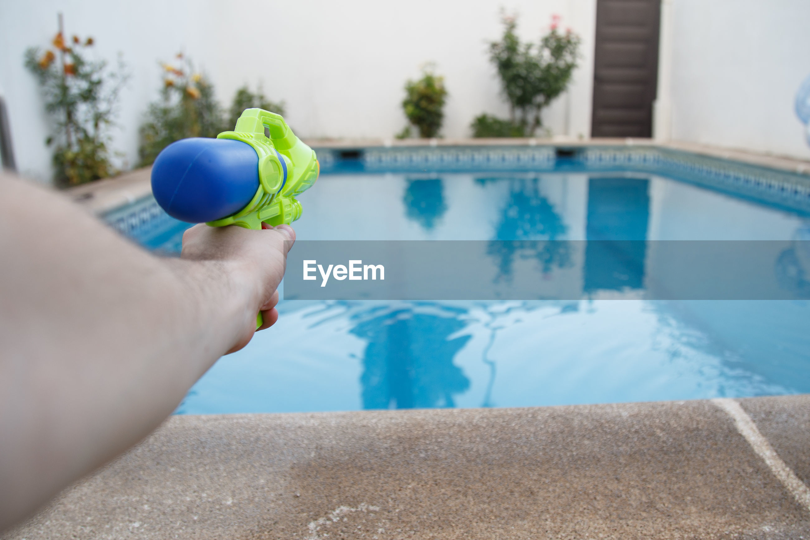 Cropped hand holding squirt gun at poolside
