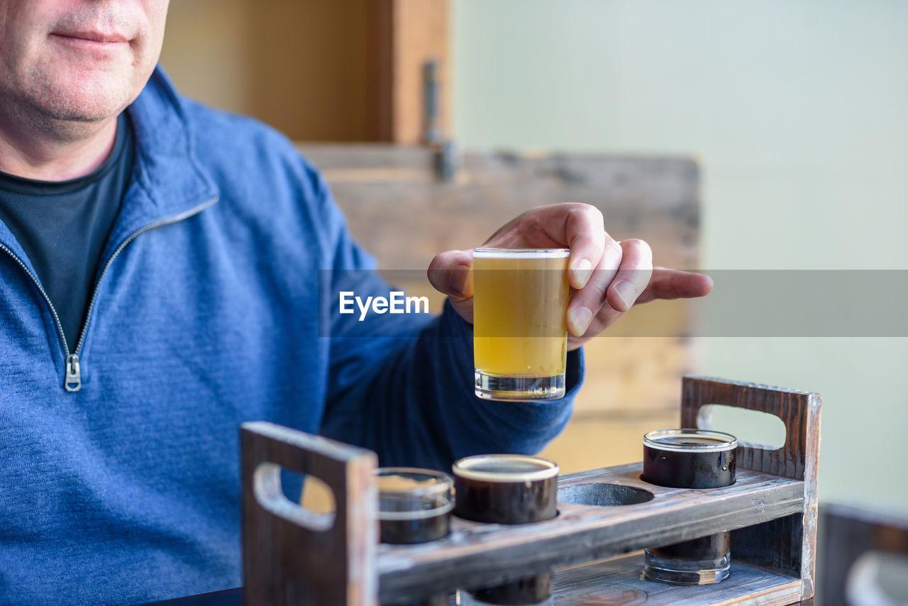 Midsection of man having beer in restaurant