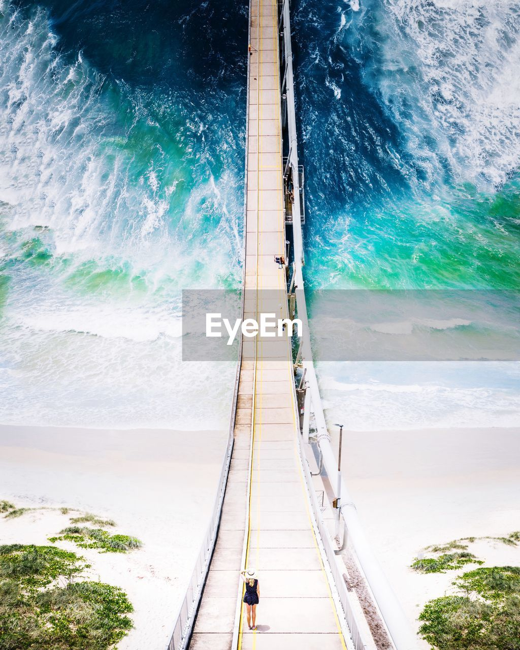 Aerial view of footbridge hanging over sea