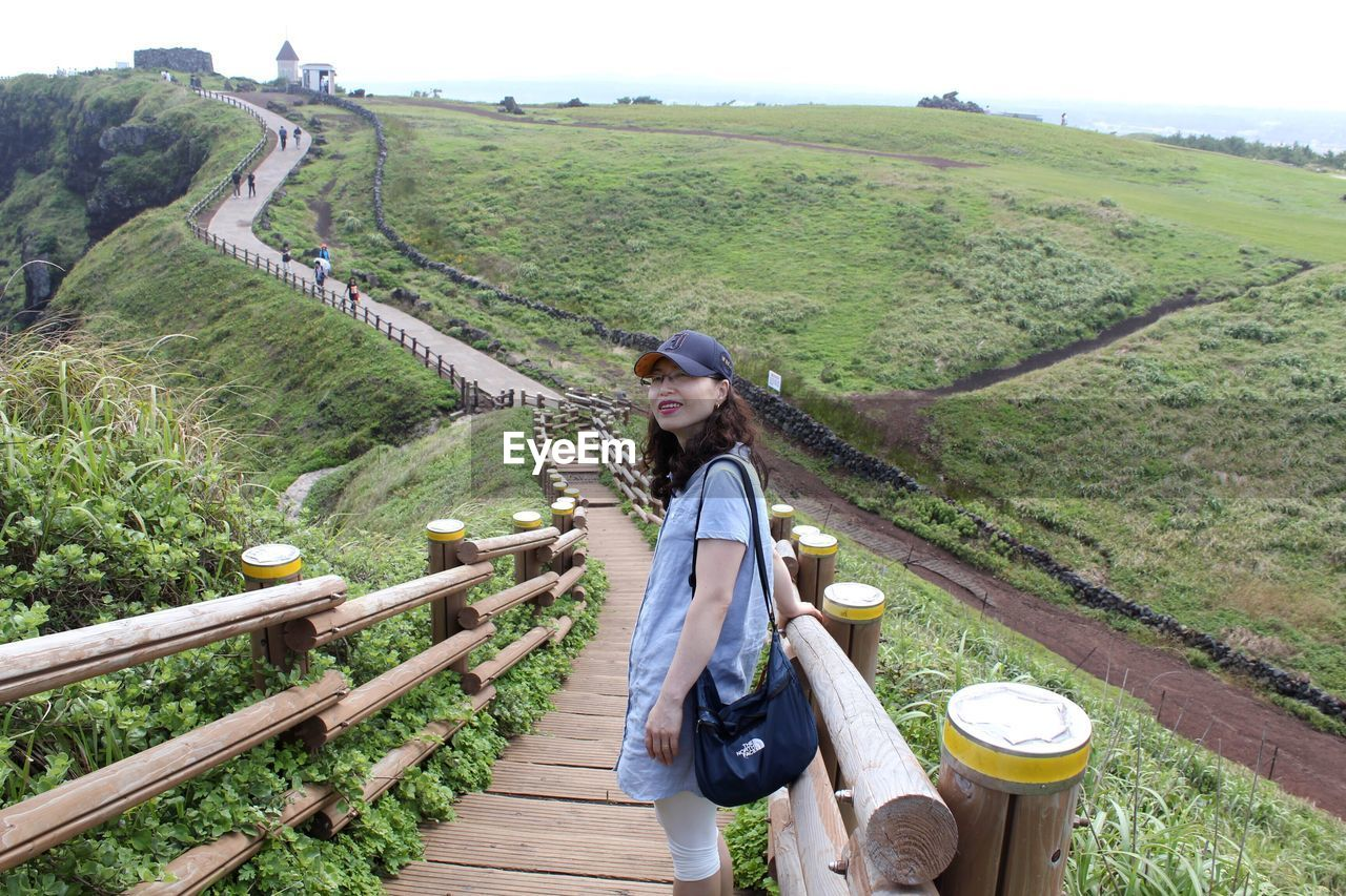 Hiker Standing On Footbridge Against Landscape