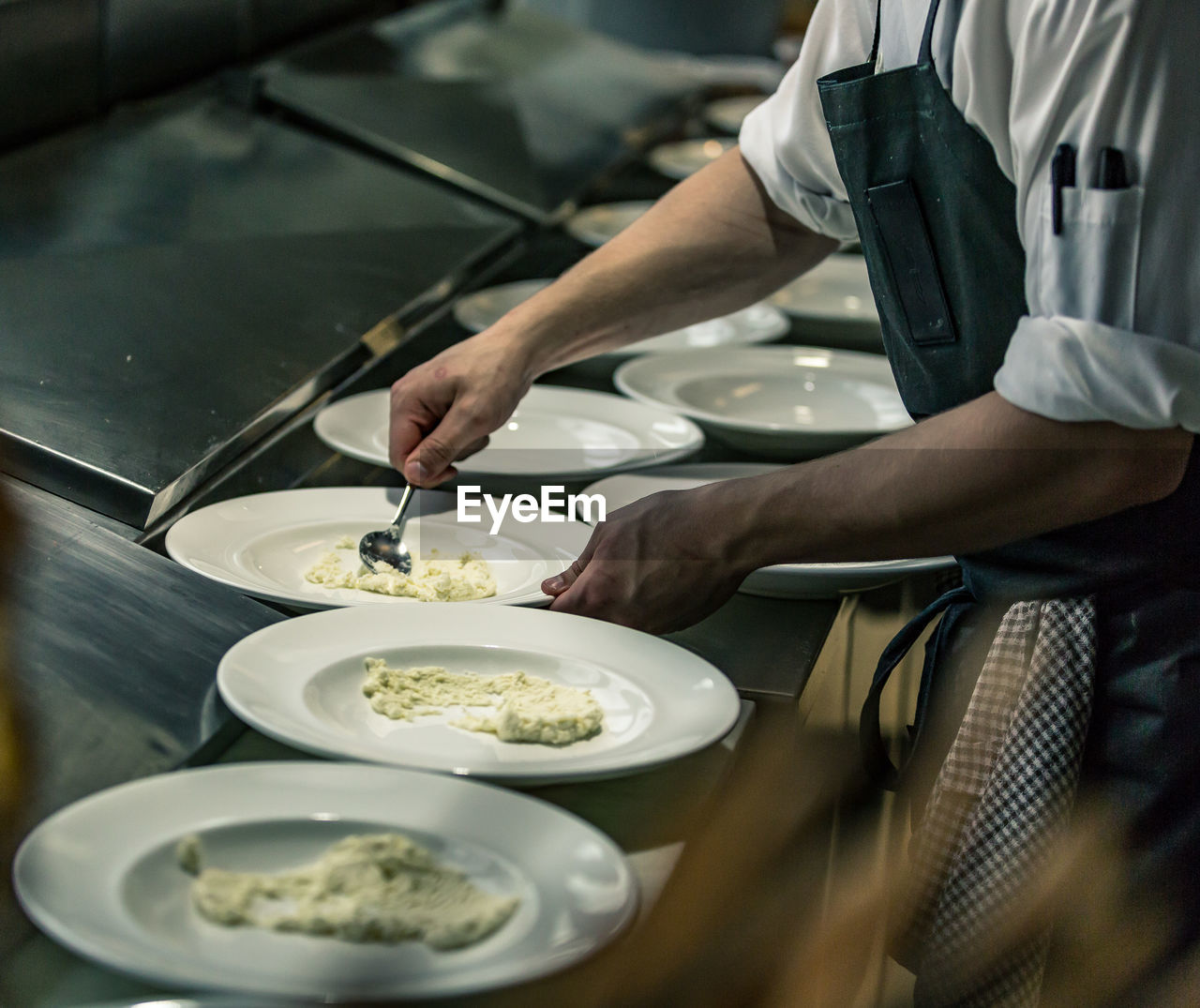 Midsection Of Chef Serving Food In Plate