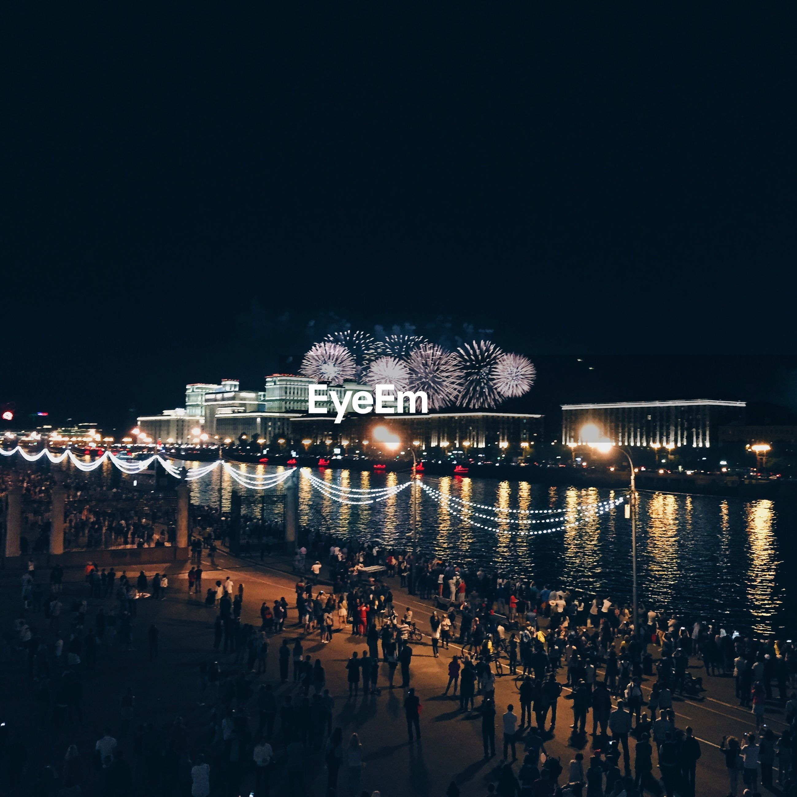 People on harbor looking at firework display above buildings against sky at night