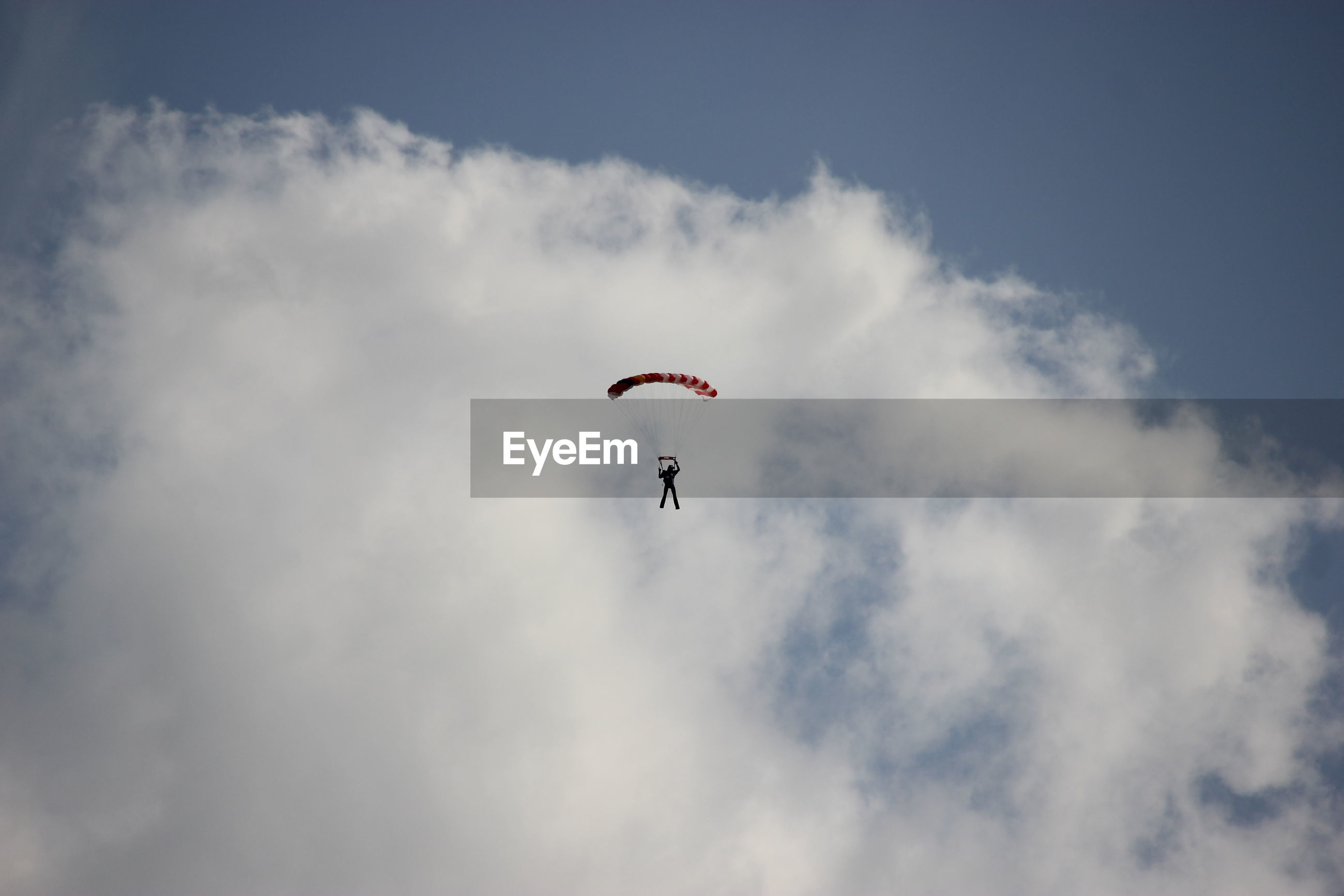 LOW ANGLE VIEW OF PERSON PARAGLIDING IN SKY