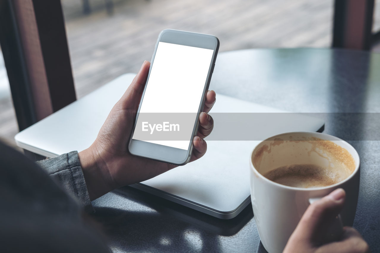 wireless technology, holding, cup, coffee, communication, portable information device, technology, coffee - drink, human hand, mug, drink, mobile phone, coffee cup, hand, human body part, smart phone, food and drink, one person, connection, screen, surfing the net, finger