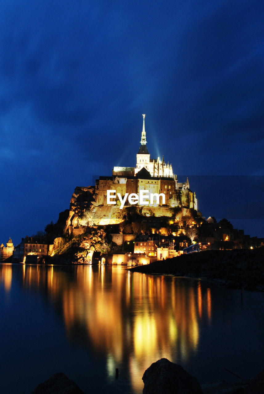Illuminated mont saint-michel by sea against sky at night
