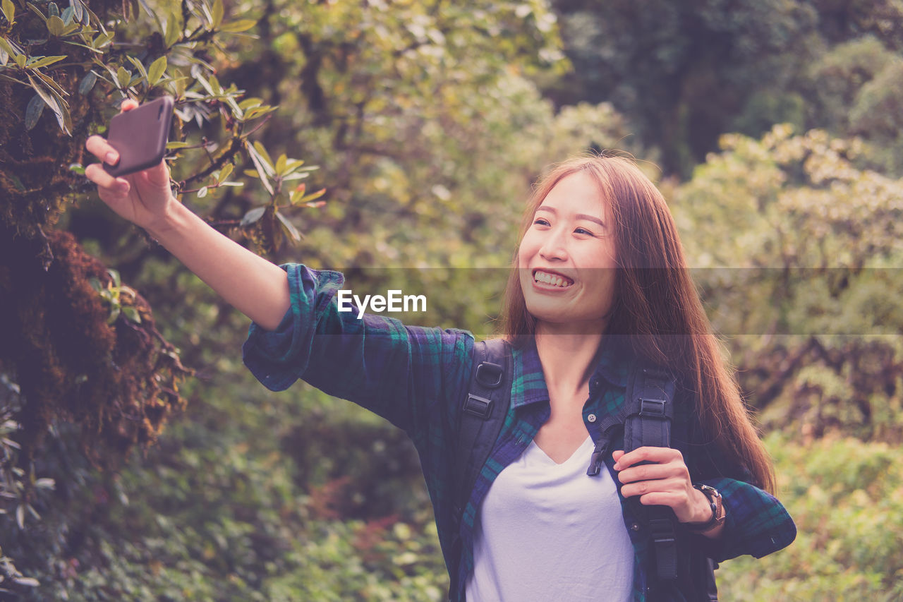 Smiling woman taking selfie with smart phone while standing against trees in forest