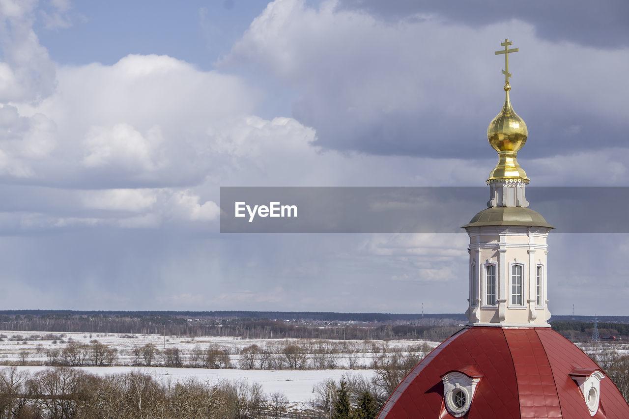 CHURCH AMIDST BUILDINGS AGAINST SKY