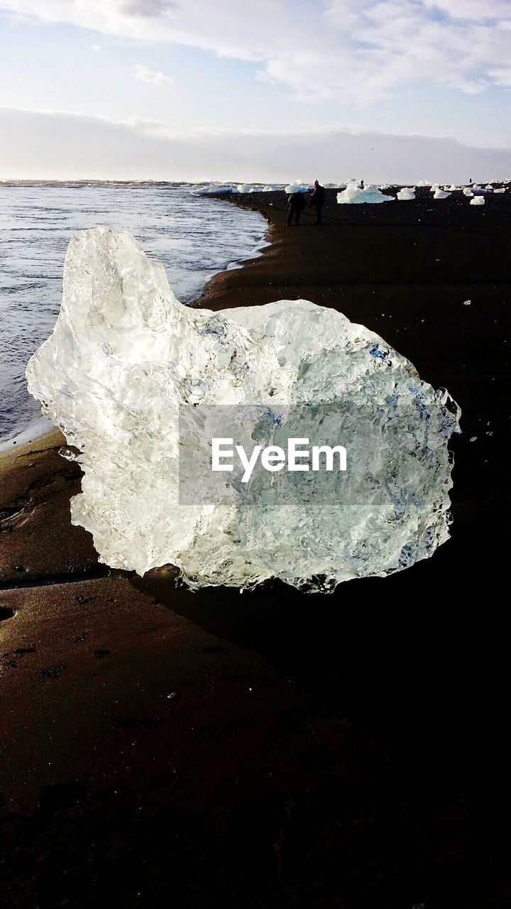 Close-Up Of Ice On Shore By Sea