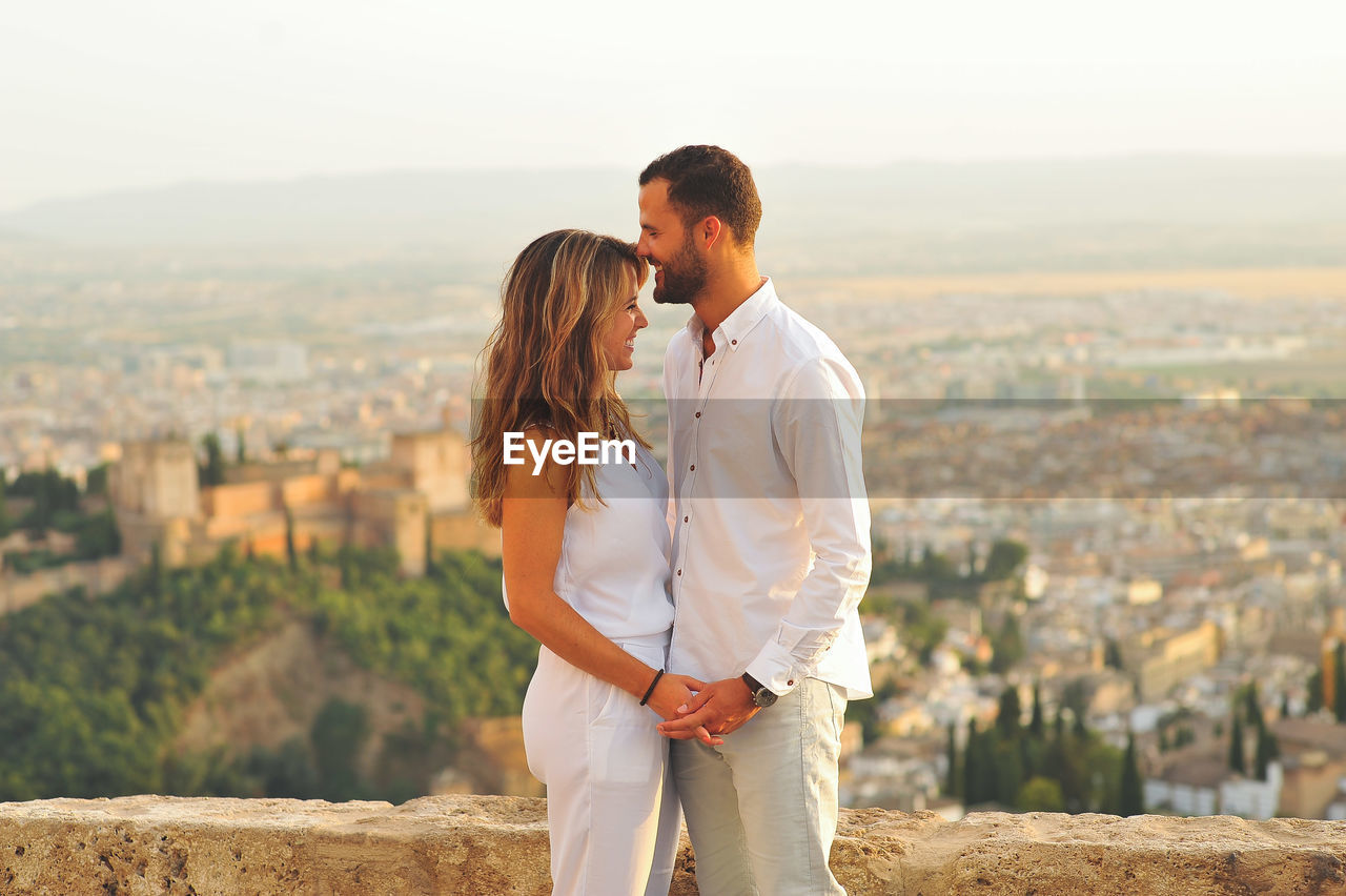 Side View Of Young Romantic Couple Standing By Retaining Wall Against City