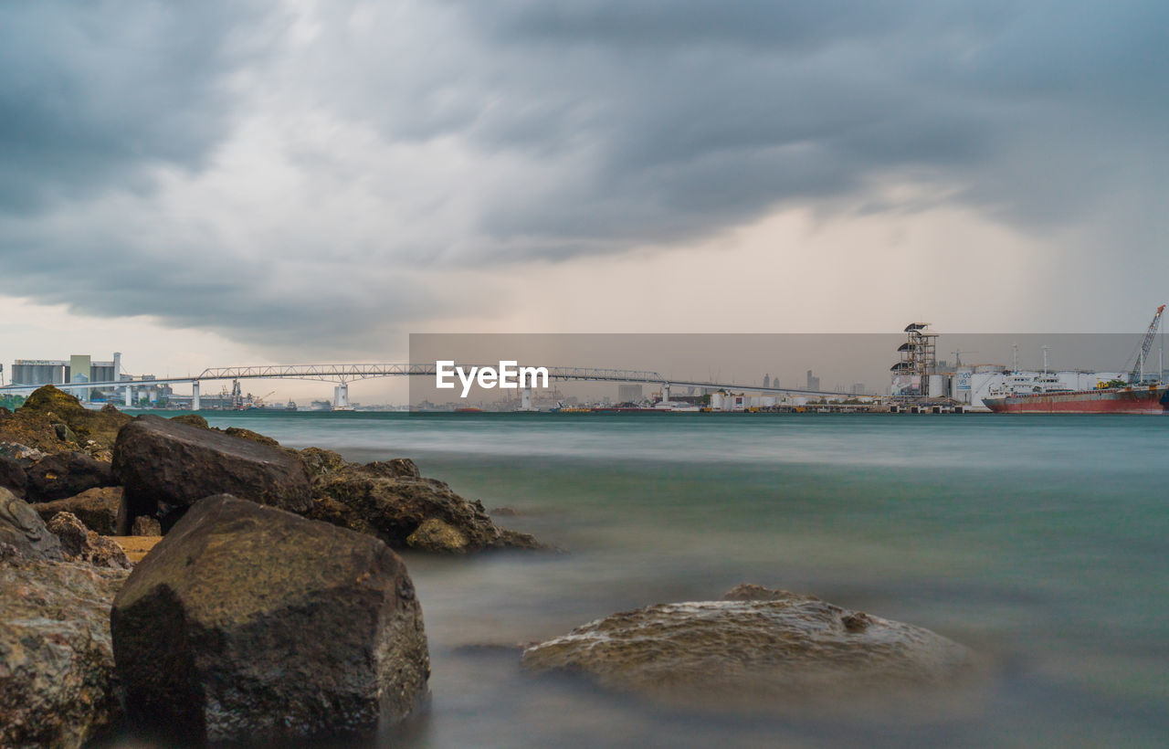 sky, cloud - sky, water, built structure, connection, architecture, bridge, rock, bridge - man made structure, rock - object, solid, nature, transportation, no people, sea, building exterior, scenics - nature, beauty in nature, outdoors, bay