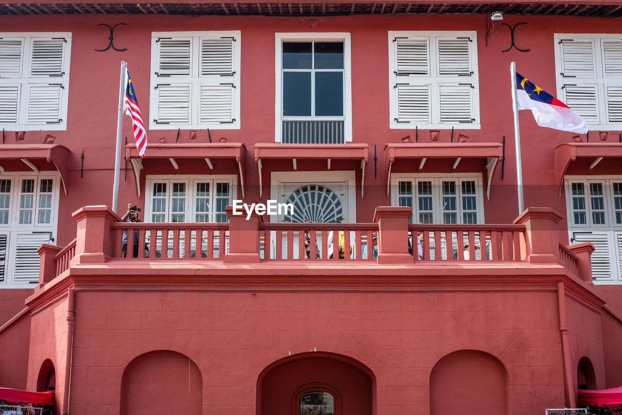 building exterior, built structure, architecture, window, red, building, no people, day, residential district, low angle view, city, outdoors, flag, full frame, balcony, glass - material, arch, backgrounds, pattern, patriotism, apartment