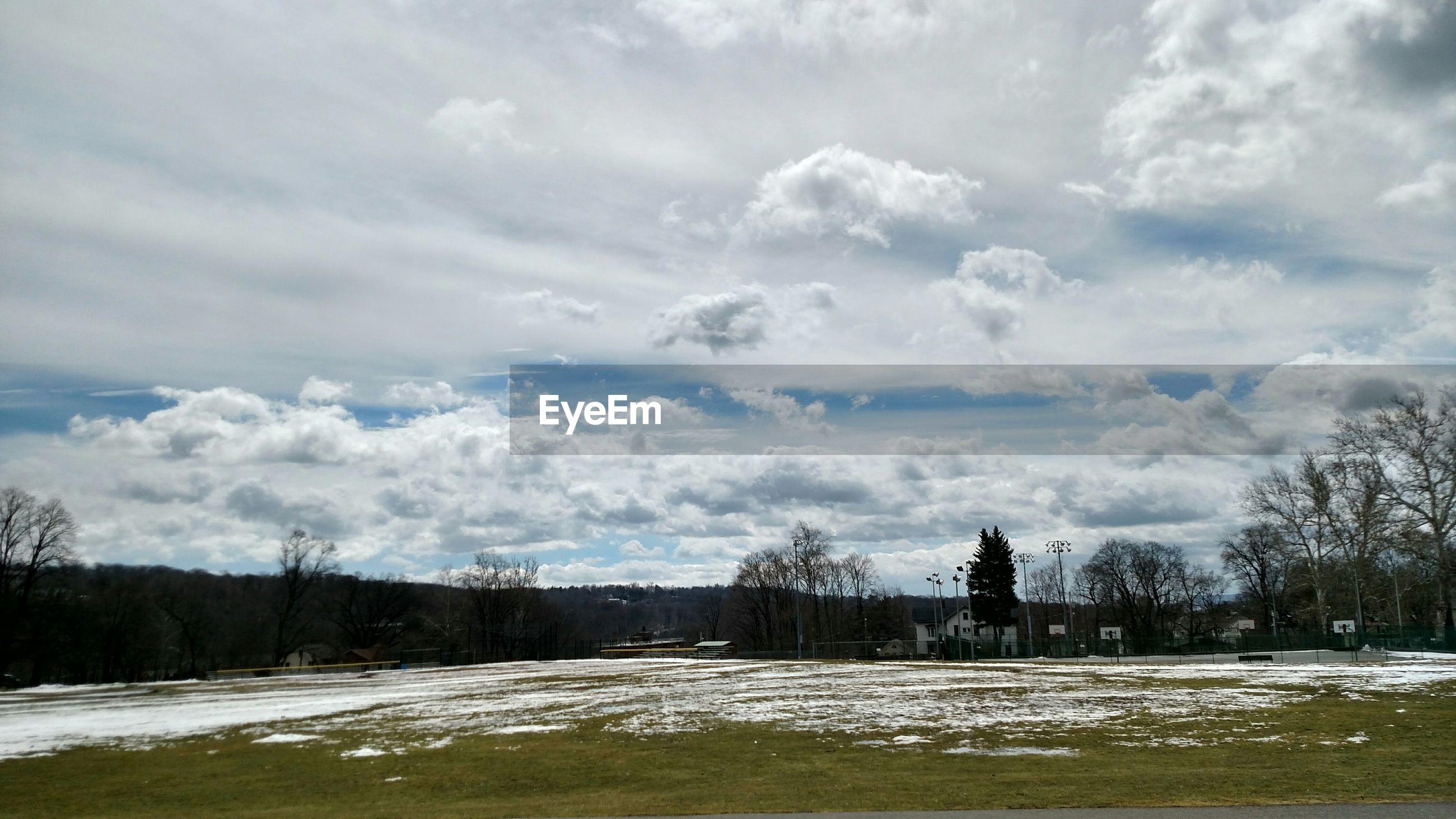 Snowy landscape against cloudy sky