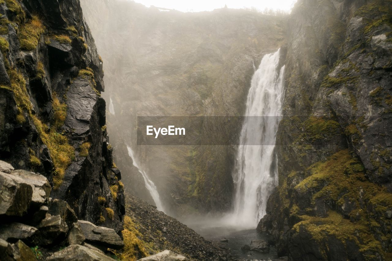 waterfall, rock, water, scenics - nature, rock - object, solid, beauty in nature, flowing water, motion, rock formation, nature, long exposure, mountain, cliff, power, blurred motion, environment, no people, power in nature, outdoors, flowing, formation, falling water