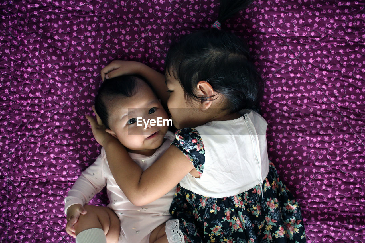 Directly Above Shot Of Girl Embracing Brother While Lying On Purple Blanket