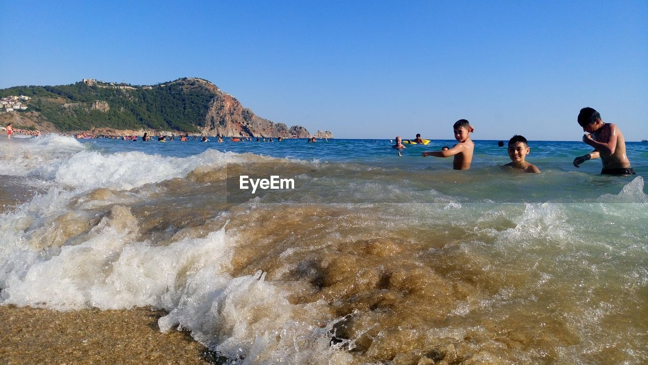 Boys Swimming In Sea Against Clear Sky