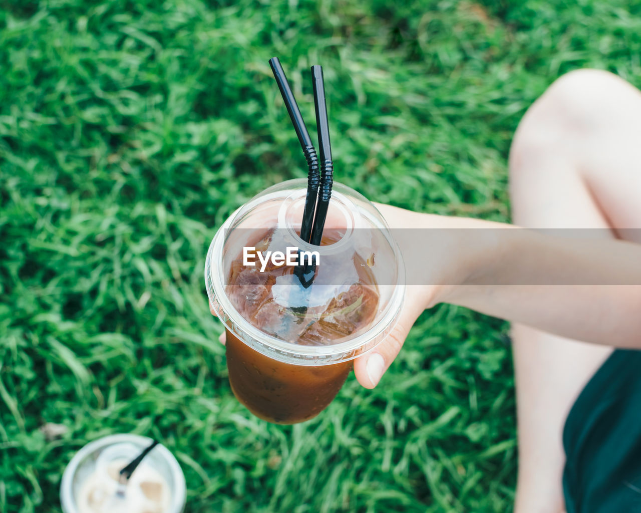 Cropped Image Of Person Holding Latte At Grassy Field