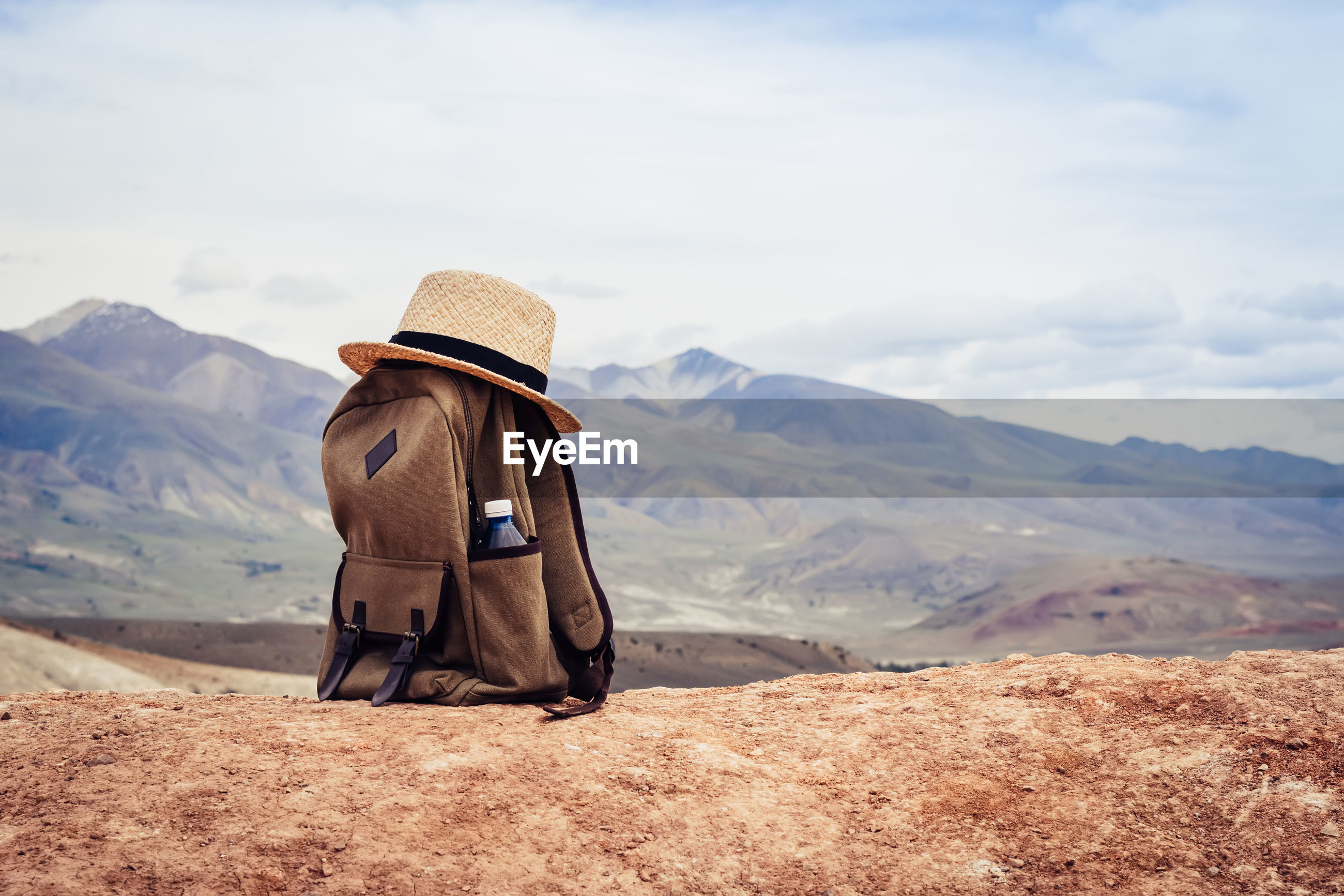 REAR VIEW OF WOMAN STANDING ON MOUNTAIN LOOKING AT MOUNTAINS