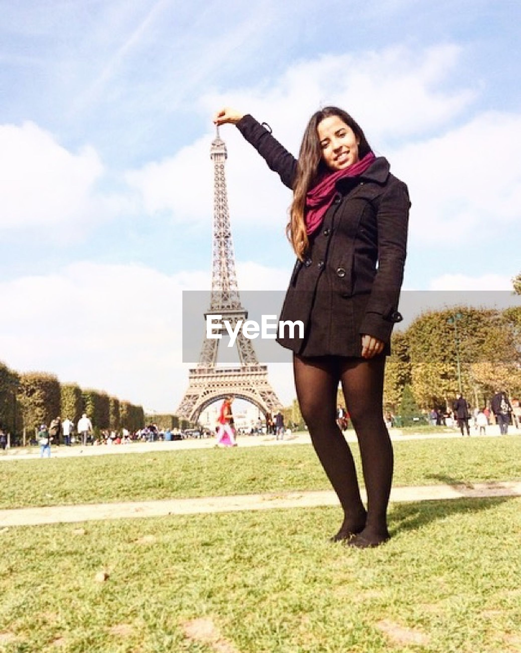grass, lifestyles, leisure activity, casual clothing, sky, architecture, tree, built structure, tourism, famous place, full length, eiffel tower, travel destinations, standing, young adult, travel, park - man made space, tourist