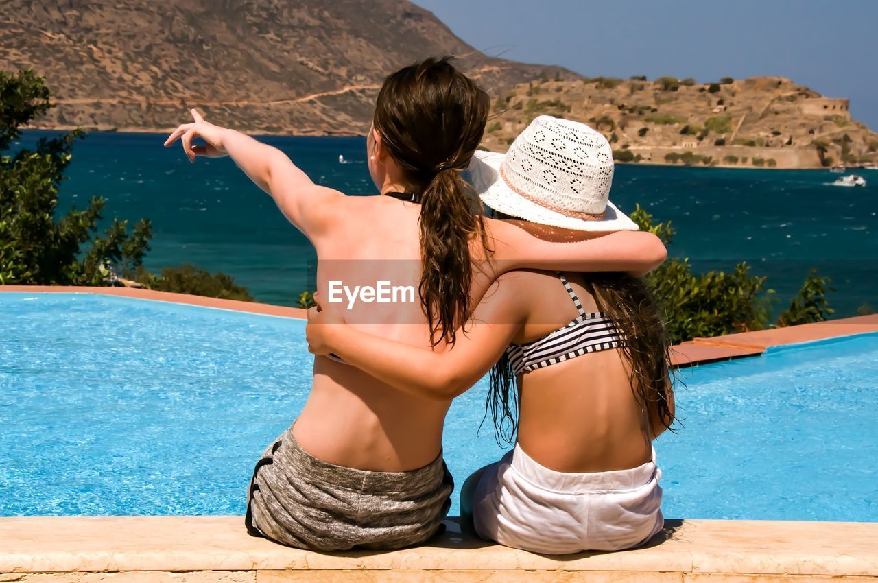 Rear View Of Sisters Sitting At Poolside On Sunny Day