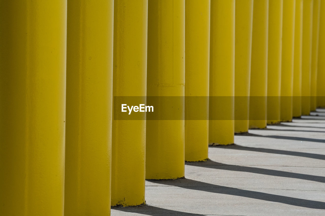 yellow, in a row, no people, sunlight, architecture, day, shadow, nature, side by side, repetition, built structure, pattern, architectural column, outdoors, wall - building feature, close-up, footpath, direction, the way forward, backgrounds, colonnade