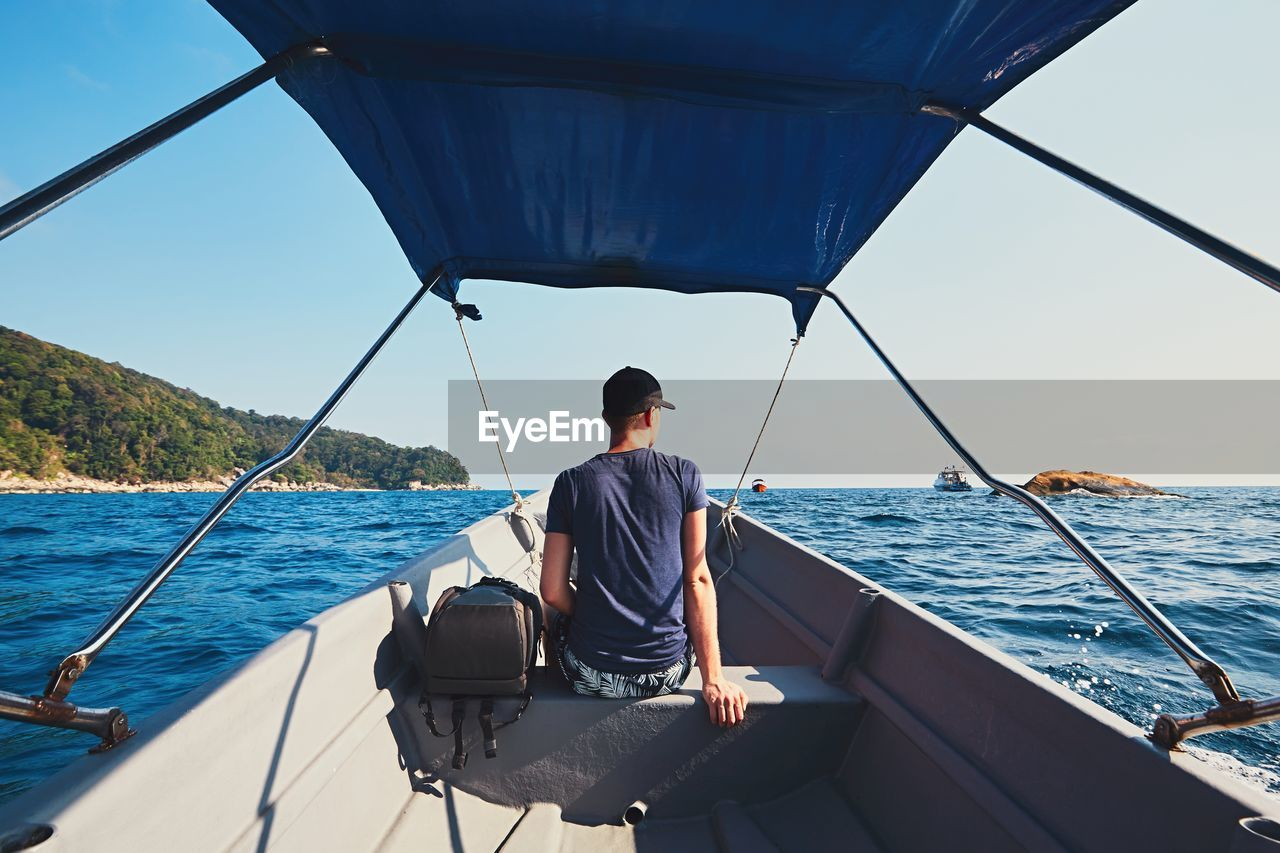 Rear View Of Man Traveling In Motorboat On Sea