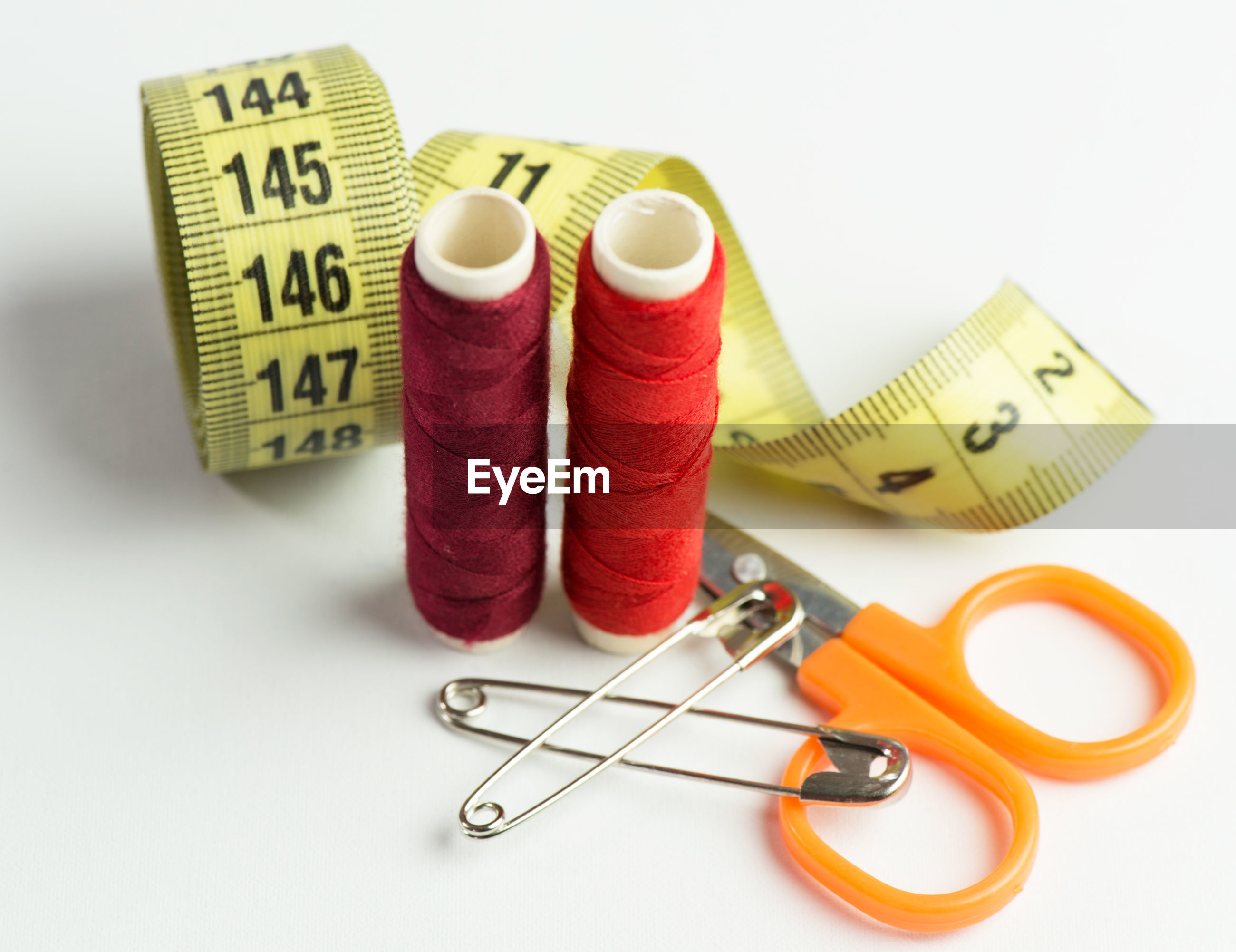Close-up of thread spools with tape measure and scissor over white background