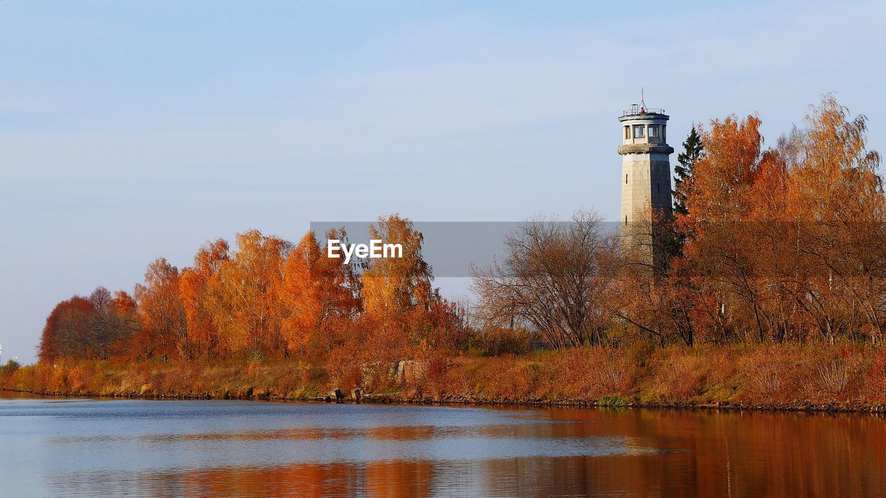 LIGHTHOUSE BY LAKE AGAINST SKY