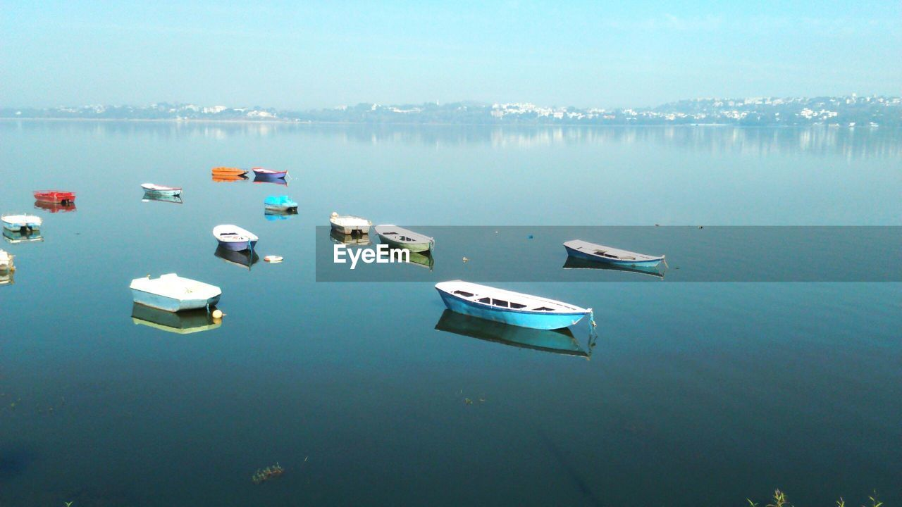 High Angle View Of Boats Moored At Lake Against Sky