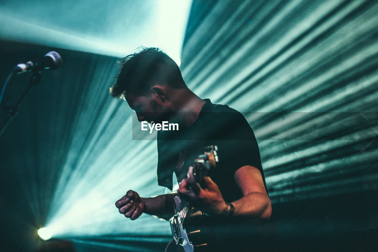 music, performance, real people, one person, event, young adult, casual clothing, skill, playing, lifestyles, arts culture and entertainment, indoors, nightlife, men, illuminated, youth culture, musician, night, musical instrument, people
