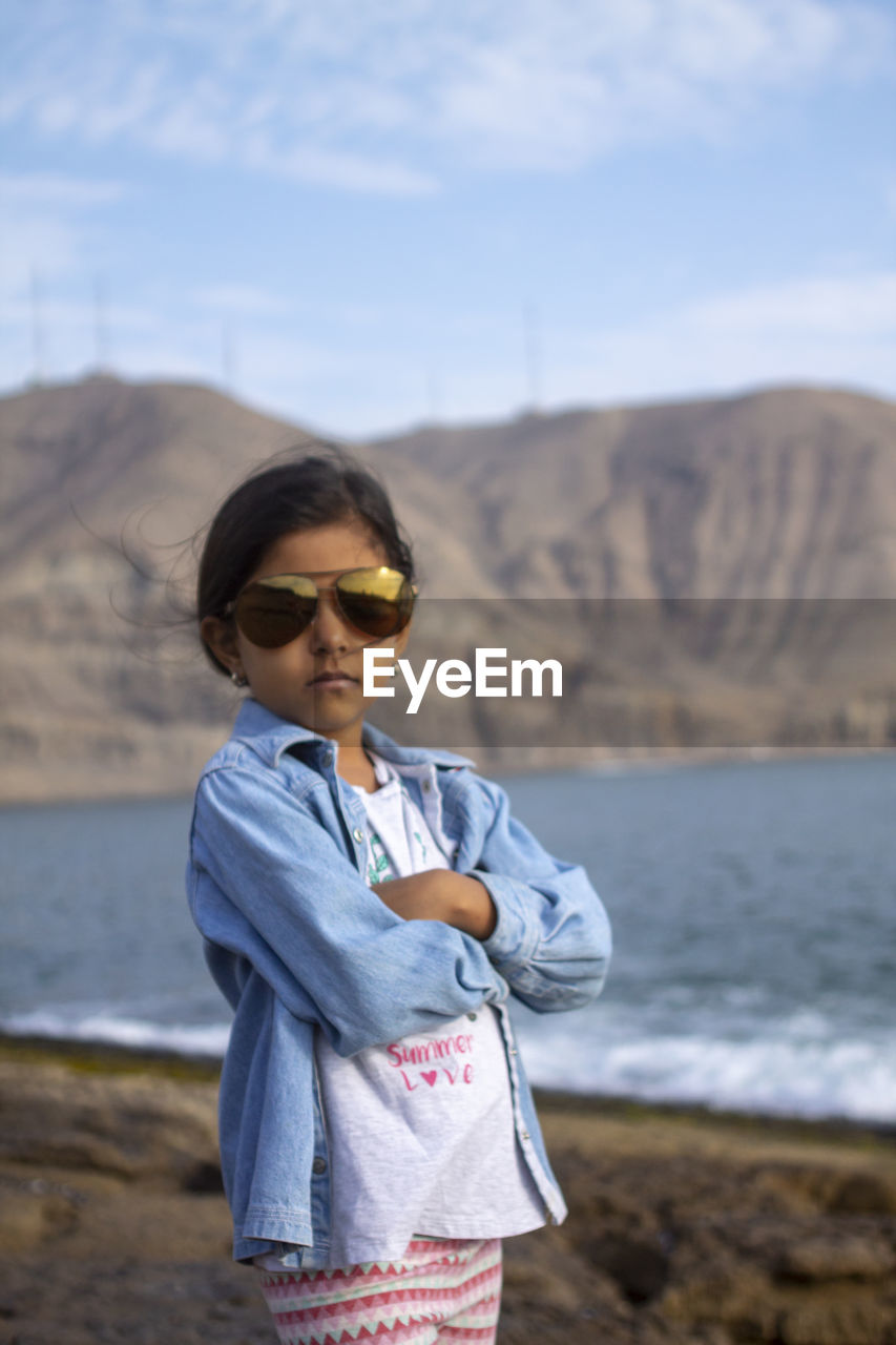 Girl Wearing Sunglasses While Standing At Beach Against Sky