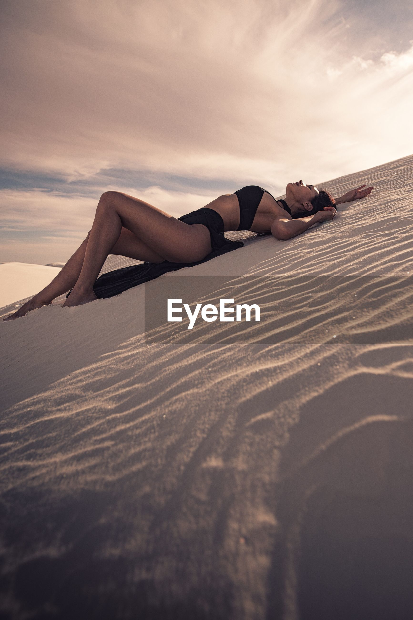 Side view of seductive woman lying on desert against sky