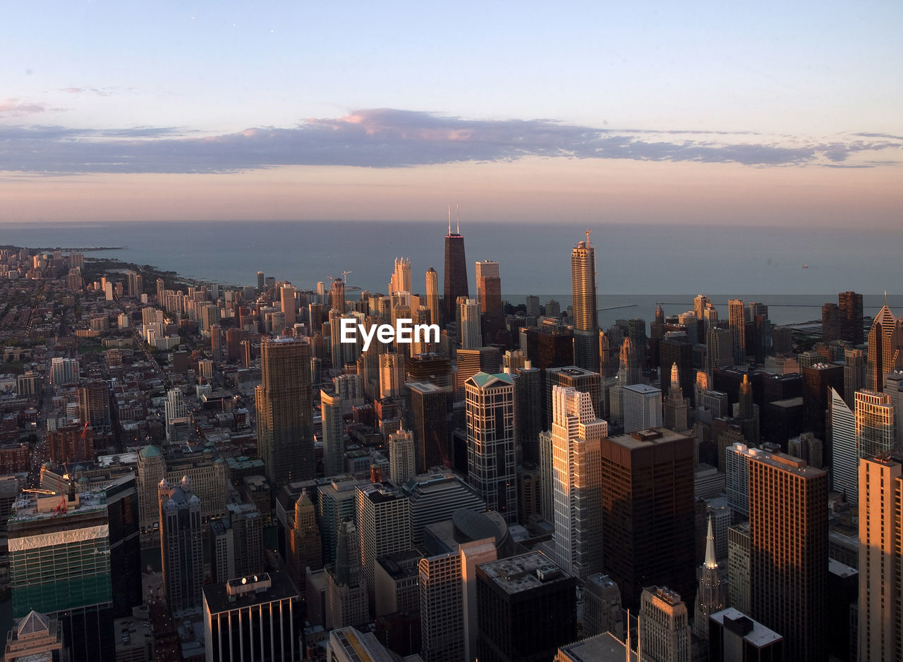 High Angle View Of Cityscape By Sea Against Sky During Sunset
